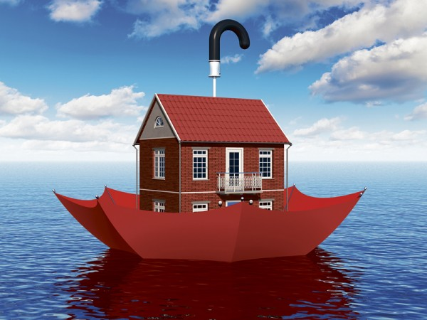Creative real estate security, home protection and insurance business concept: residential house cottage floating in blue sea water ocean in red umbrella parasol Real estate insurance concept